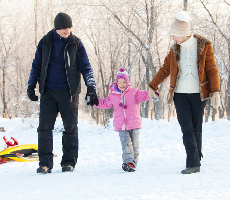 Mother and Father walking with young girl on a snowy winter day