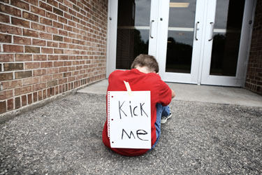 Developmental Trauma, A child sitting in front of a school entry way with a sign taped to his back that reads Kick Me