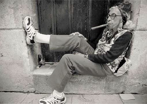 Photo of an old woman smoking a cigar.