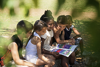 Children sitting clustered reading a book outdoors.
